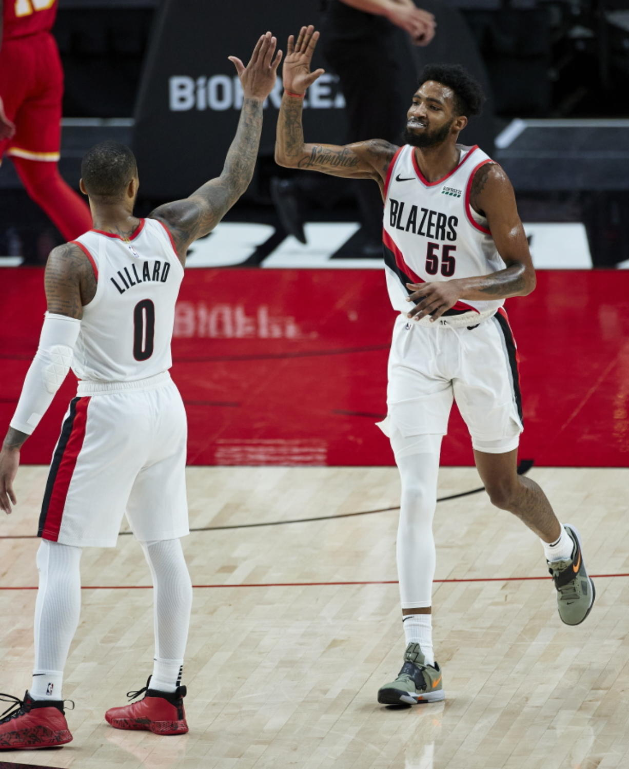 Portland Trail Blazers forward Derrick Jones Jr., right, high-fives guard Damian Lillard after Jones scored against the Atlanta Hawks during the second half of an NBA basketball game in Portland, Ore., Saturday, Jan. 16, 2021.