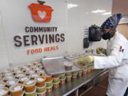 Chef Jermaine Wall stacks containers of soups at Community Servings, which prepares and delivers scratch-made, medically tailored meals to individuals & families living with critical & chronic illnesses, Tuesday, Jan. 12, 2021, in the Jamaica Plain neighborhood of Boston. Food is a growing focus for insurers as they look to improve the health of the people they cover and cut costs. Insurers first started covering Community Servings meals about five years ago, and CEO David Waters says they now cover close to 40%.