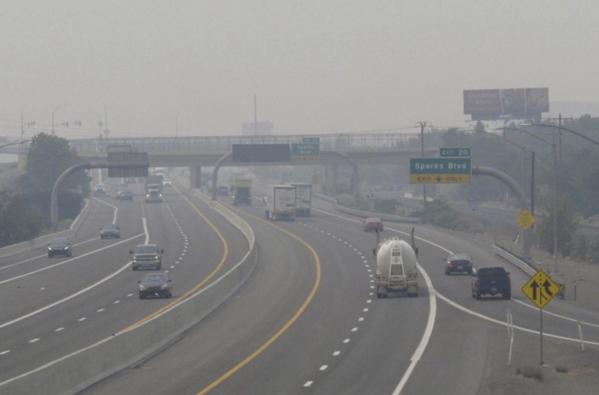 """FILE - In this Wednesday, Aug. 19, 2020. file photo, smoke from California wildfires up to 200 miles away obscures the view of traffic traveling on Interstate 80, looking west in Sparks, Nev. Local schools canceled all outdoor activities as the air quality index approached the """"very unhealthy"""" category for the general population Wednesday afternoon."""