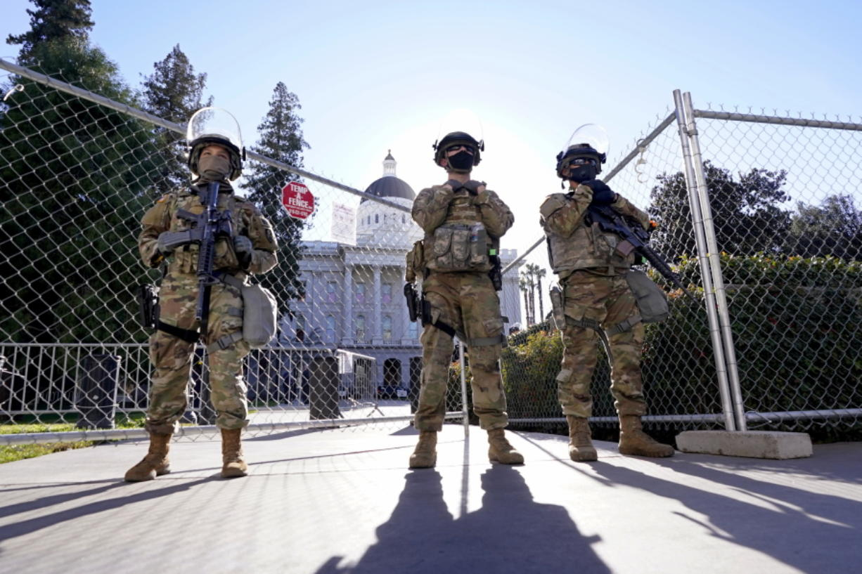 California National Guard members stand guard at an access point to the California state Capitol in Sacramento, Calif., Tuesday, Jan. 19, 2021. A temporary 6-foot high chain link fence surrounds the Capitol and California Gov. Gavin Newsom mobilized the National Guard last week over concerns that protests around Wednesday's inauguration of President-elect Joe Biden could turn violent and destructive.
