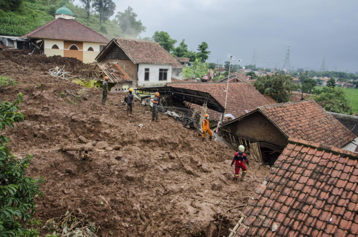 Rescuers search for victims at a village hit by Sunday's landslides in Sumedang, West Java, Indonesia, Monday, Jan. 11, 2021. Landslides triggered by heavy rain in the village left at a number of people died and injured, officials said.