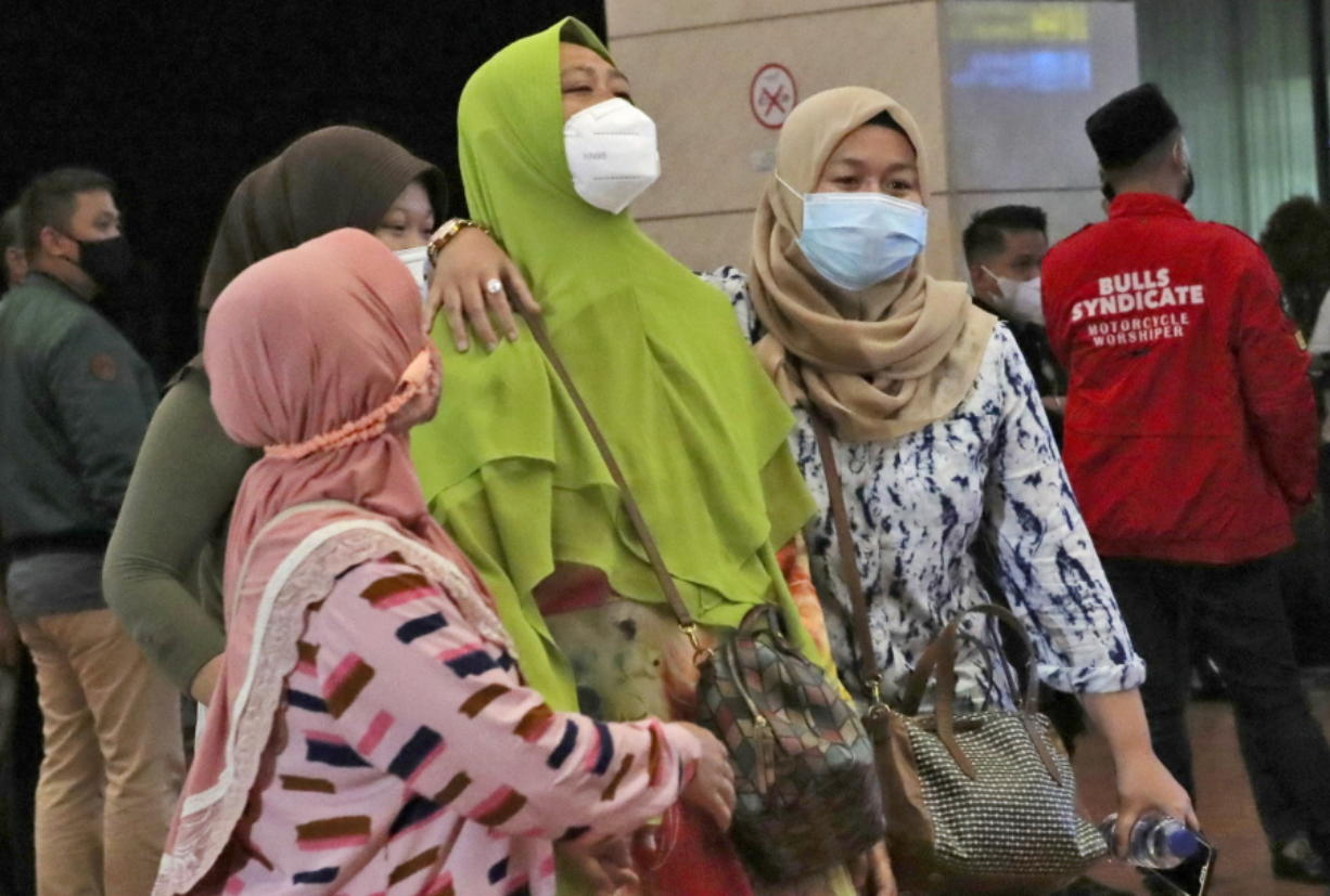 Relatives of passengers arrive at a crisis center set up following a report that a Sriwijaya Air passenger jet has lost contact with air traffic controllers shortly after take off, at Soekarno-Hatta International Airport in Tangerang, Indonesia,Saturday, Jan. 9, 2021. The Boeing 737-500 took off from Jakarta with 56 passengers and six crew members onboard, and lost contact with the control tower a few moments later.