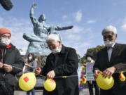 Participants deflate balloons in hope of neutralizing and demolishing nuclear warheads, during a memorial gathering at Peace Park in Nagasaki, southern Japan Friday, Jan. 22, 2021. The first-ever treaty to ban nuclear weapons entered into force on Friday, hailed as a historic step to rid the world of its deadliest weapons but strongly opposed by the world's nuclear-armed nations.