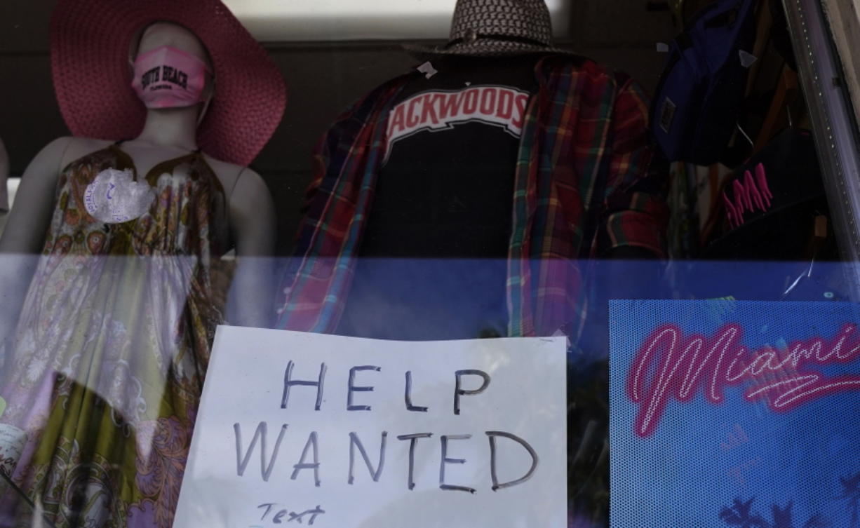 "A ""Help Wanted,"" sign is shown in the window of a souvenir shop, Thursday, Jan. 7, 2021, in Miami Beach, Fla.  Layoffs spiked in November compared with the previous month and the number of job openings slipped, a sign the job market has stalled as the resurgent coronavirus has forced new shutdowns of restaurants and bars and discouraged consumer spending."