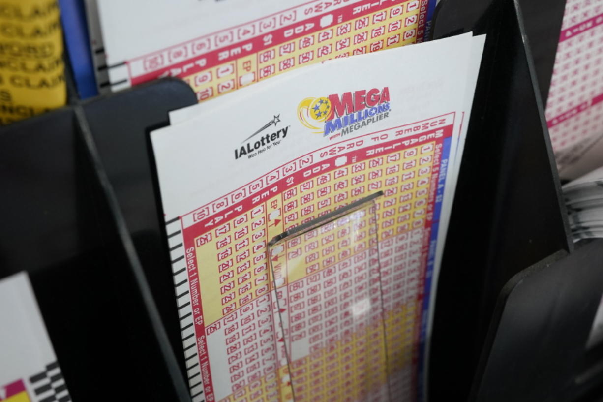 Blank forms for the Mega Millions lottery sit in a bin at a local grocery store, Tuesday, Jan. 12, 2021, in Des Moines, Iowa. Lottery players have a chance to win the largest jackpots in nearly two years as Tuesday's Mega Millions has grown to an estimated $625 million and Wednesday's Powerball to an estimated $550 million.
