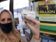 A patron, who did not want to give her name, shows the ticket she had just purchased for the Mega Millions lottery drawing at the lottery ticket vending kiosk in a Smoker Friendly store, Friday, Jan. 22, 2021, in Cranberry Township, Pa. The jackpot for the Mega Millions lottery game has grown to $1 billion ahead of Friday night's drawing after more than four months without a winner.