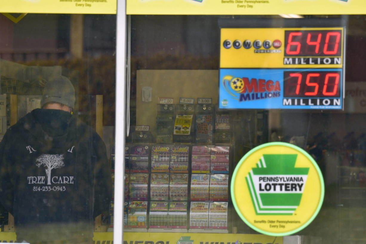 A lottery customer purchases lottery tickets at Conjelko's Dairy Store in Windber, Pa., as the Mega Millions grew to $750 million and the PowerBall to $ 640 Million on Thursday, Jan. 14, 2021.