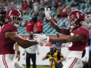 Alabama wide receiver John Metchie III, left, congratulates wide receiver DeVonta Smith, after Smith scored a touchdown against Ohio State during the first half of an NCAA College Football Playoff national championship game, Monday, Jan. 11, 2021, in Miami Gardens, Fla.