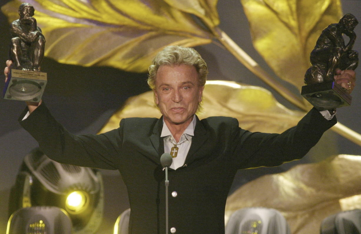 """FILE - German illusionist Siegfried Fischbacher of the duo """" Siegfried & Roy"""" holds their trophies after receiving the World Entertainment Award at the World Award 2003 ceremony in Hamburg, northern Germany, on Oct.22, 2003. German news agency dpa is reporting that  Fischbacher, the surviving member of duo Siegfried & Roy has died in Las Vegas at age 81. The news agency said Thursday that Fischbacher's sister, a nun who lives in Munich, confirmed his death of cancer."""