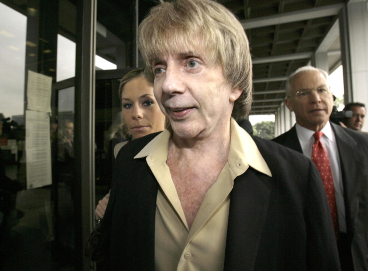 """FILE - In this March 19, 2007 file photo, music producer Phil Spector and his attorney, Roger Rosen, right, leave Los Angeles Superior Court for a break during the start of jury selection in Spectors' murder trial.  Spector, the eccentric and revolutionary music producer who transformed rock music with his """"Wall of Sound"""" method and who was later convicted of murder, died Saturday, Jan. 16, 2021, at age 81."""