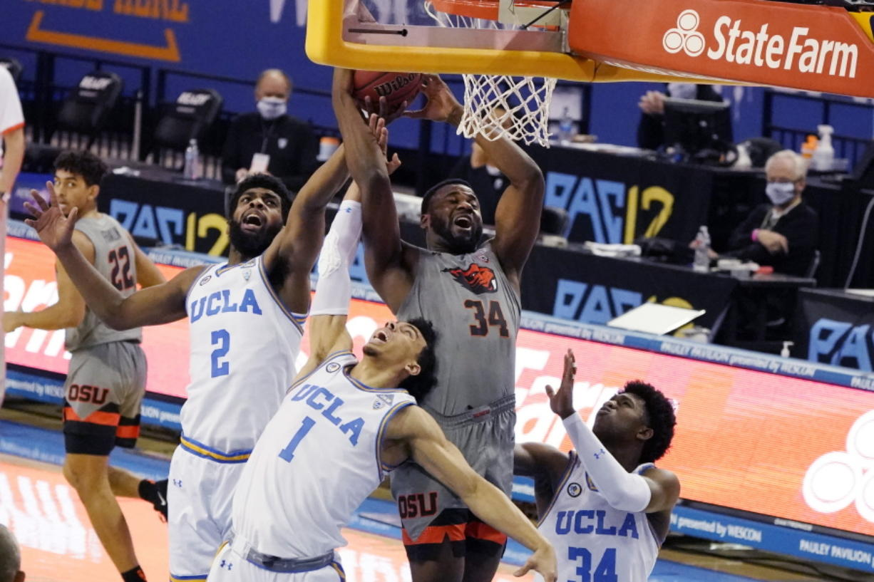 Oregon State forward Rodrigue Andela (34) grabs rebound over UCLA forward Cody Riley (2) and guard Jules Bernard (1) during the first half of an NCAA college basketball game Saturday, Jan. 30, 2021, in Los Angeles.