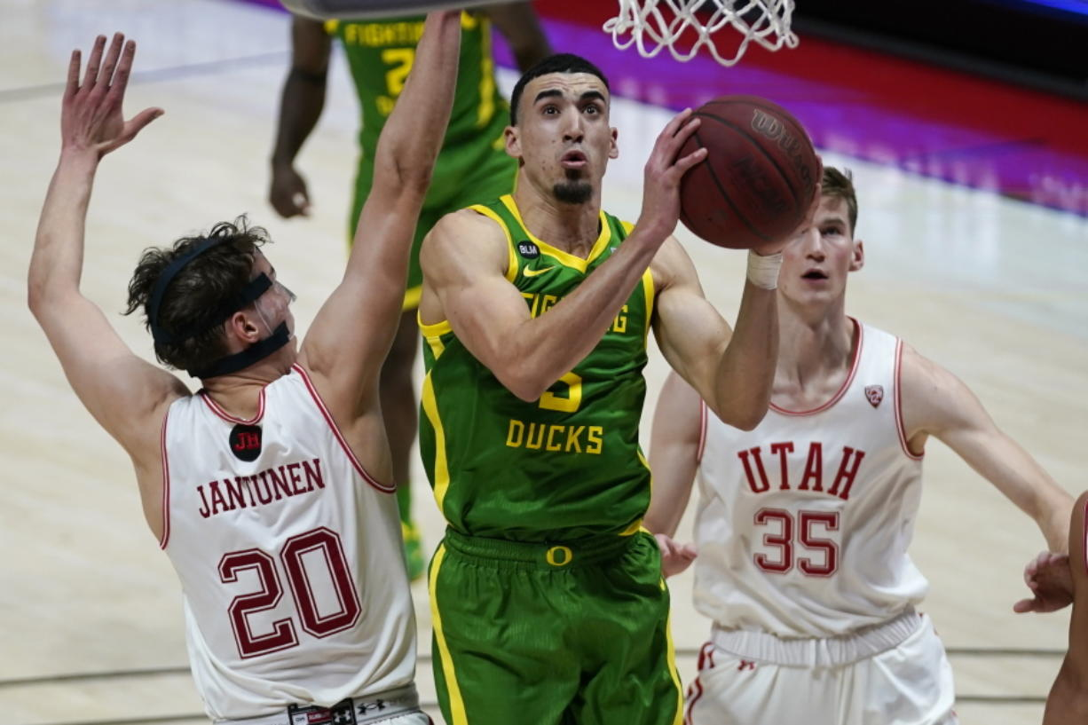 Oregon guard Chris Duarte, center, goes to the basket as Utah's Mikael Jantunen (20) and Branden Carlson (35) defend in the first half during an NCAA college basketball game Saturday, Jan. 9, 2021, in Salt Lake City.