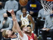 Indiana Pacers forward Domantas Sabonis, left, and Portland Trail Blazers center Jusuf Nurkic reach for a rebound during the first half of an NBA basketball game in Portland, Ore., Thursday, Jan. 14, 2021.