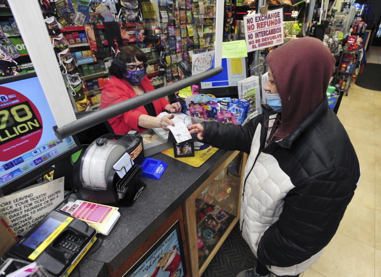 Jacqueline Donahue of Hazleton, right, buys la Mega Millions lottery ticket at the Anthracite Newsstand on Public Square, Monday, Jan. 18, 2021, in Wilkes-Barre, Pa.