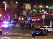 Tacoma Police and other law enforcement officers stand in an intersection near the site of a car crash Saturday in downtown Tacoma. At least one person was injured when a police car plowed through a crowd of people Saturday night who were watching a downtown street race, the Tacoma News-Tribune reported. (AP Photo/Ted S.