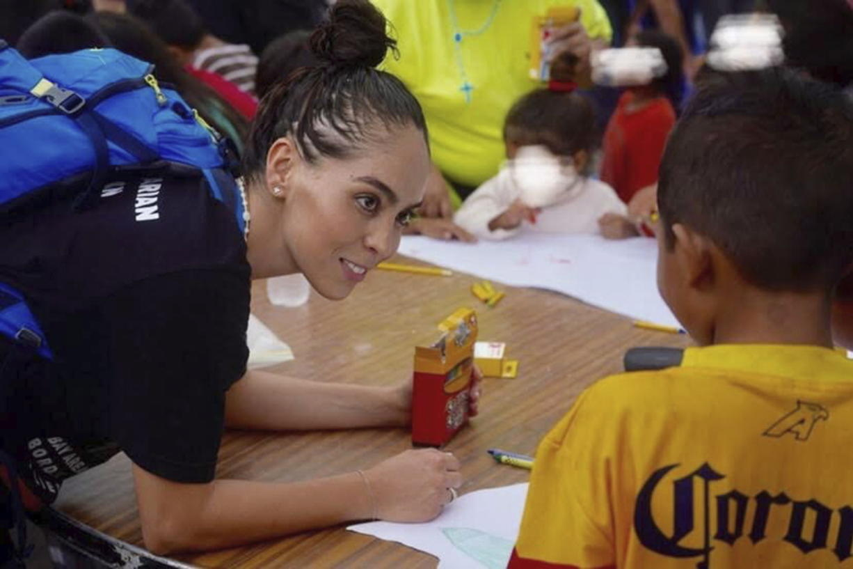 In this October 2019 photo provided by Pocho Sanchez, Daniela Dominguez, assistant professor in counseling psychology at University of San Francisco, draws and chats with children from Honduras at a migrant camp in Matamoros, Mexico. Dominguez said mutual aid networks are part of the Latino culture where people may feel safer getting help from their own community rather than government entities or formal charities.