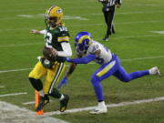 Green Bay Packers quarterback Aaron Rodgers scores on a one-yard touchdown run past Los Angeles Rams' John Johnson during the first half of an NFL divisional playoff football game, Saturday, Jan. 16, 2021, in Green Bay, Wis.