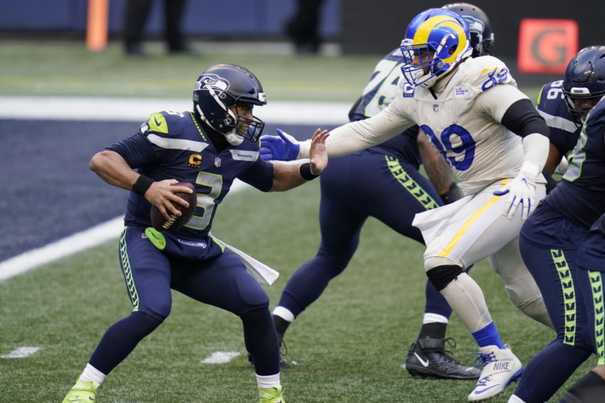 Seattle Seahawks quarterback Russell Wilson (3) tries to fend off a sack by Los Angeles Rams defensive lineman Aaron Donald (99) during the second half of an NFL football game, Sunday, Dec. 27, 2020, in Seattle.