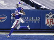 Buffalo Bills' Taron Johnson (24) returns an interception for a touchdown during the second half of an NFL divisional round football game against the Baltimore Ravens Saturday, Jan. 16, 2021, in Orchard Park, N.Y.