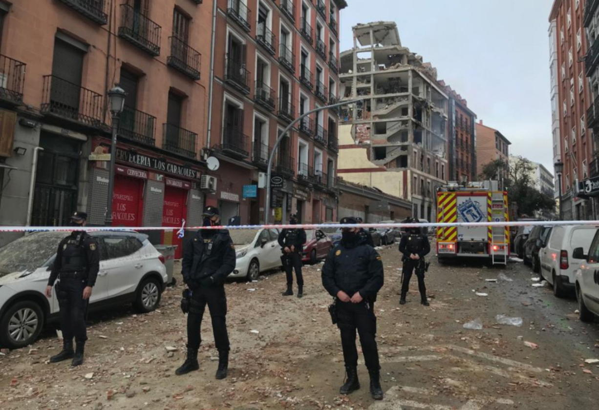 Police officers cordon off Toledo Street following an explosion in downtown Madrid, Spain, Wednesday, Jan. 20, 2021. A loud explosion of unknown origin has partially destroyed a six-floor-tall building flanked by a school and a nursing home in the center of Spain's capital, Madrid.