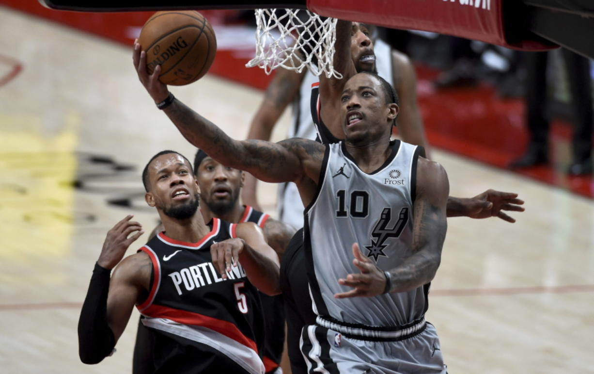 San Antonio Spurs forward DeMar DeRozan, right, drives to the basket on Portland Trail Blazers guard Rodney Hood, right, during the second half of an NBA basketball game in Portland, Ore., Monday, Jan. 18, 2021.
