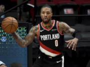 Portland Trail Blazers guard Damian Lillard passes the ball during the second half of an NBA basketball game against the San Antonio Spurs in Portland, Ore., Monday, Jan. 18, 2021. The Spurs won 125-104.