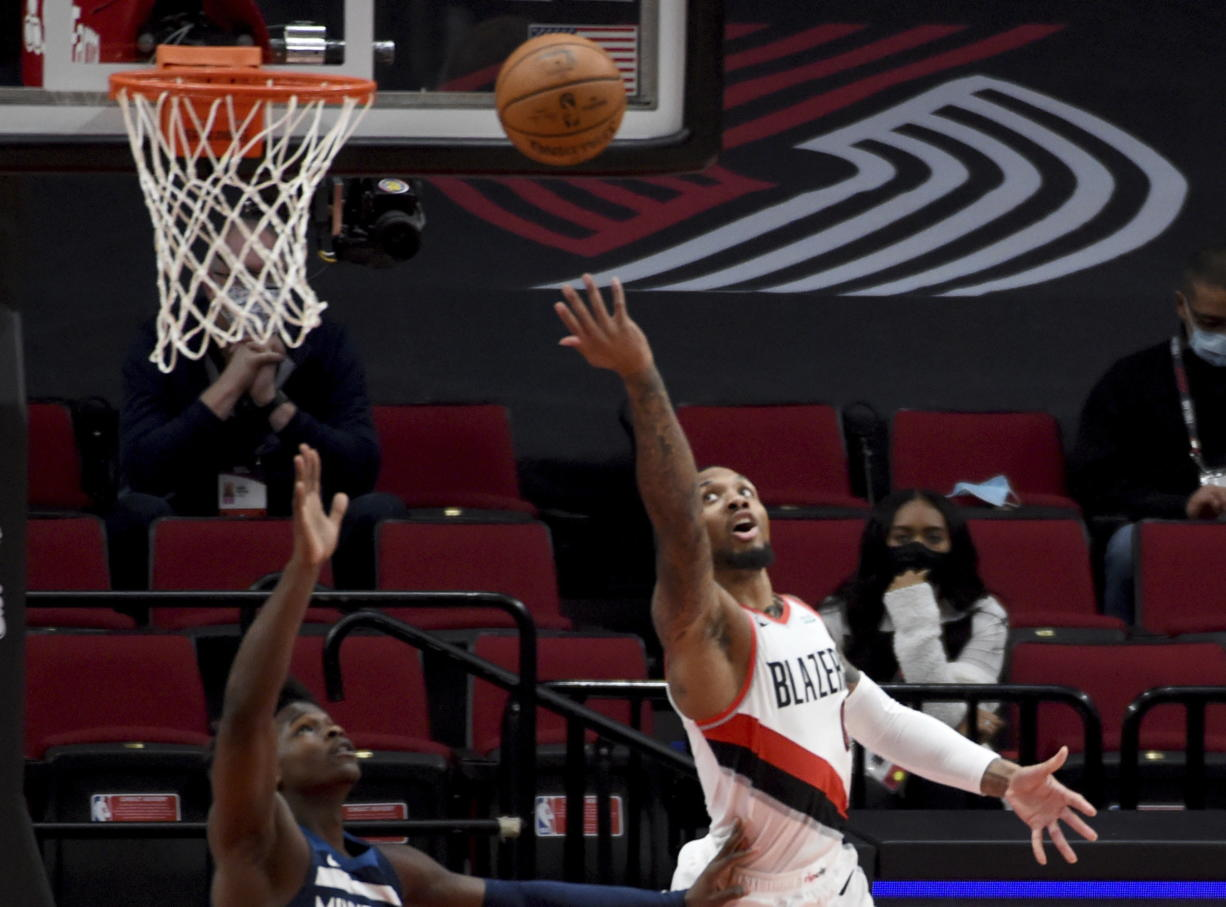 Portland Trail Blazers guard Damian Lillard, right, lays the ball in over Minnesota Timberwolves guard Anthony Edwards, left, during the first half of an NBA basketball game in Portland, Ore., Thursday, Jan. 7, 2021.
