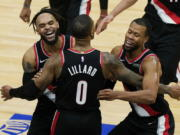 Portland Trail Blazers guard Damian Lillard (0) celebrates with guards Gary Trent Jr., left, and Rodney Hood after making the winning three-point basket during the second half of an NBA basketball game against the Chicago Bulls in Chicago, Saturday, Jan. 30, 2021. (AP Photo/Nam Y.
