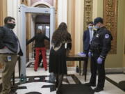 Congressional staff passes through a metal detector and security screening as they enter the House chamber, new measures put into place after a mob loyal to President Donald Trump stormed the Capitol, in Washington, Tuesday, Jan. 12, 2021. Democrats are set to pass a resolution calling on Vice President Mike Pence to invoke constitutional authority under the 25th Amendment to oust Trump. (AP Photo/J.