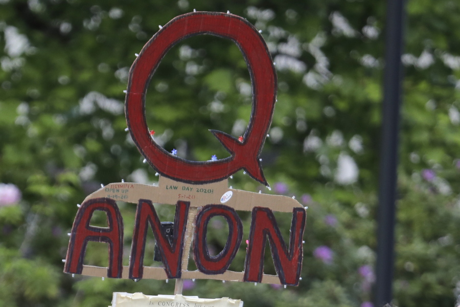 FILE - In this May 14, 2020, file photo, a person carries a sign supporting QAnon during a protest rally in Olympia, Wash, USA.  The social media company Twitter said Tuesday Jan. 12, 2021, it has suspended more than 70,000 accounts associated with the far right QAnon conspiracy theory following last week's U.S. Capitol insurrection. (AP Photo/Ted S.