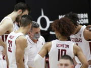 Washington State coach Kyle Smith, center, talks to the team during a break in play in the second half of an NCAA college basketball game against Utah in Pullman, Wash., Thursday, Jan. 21, 2021.