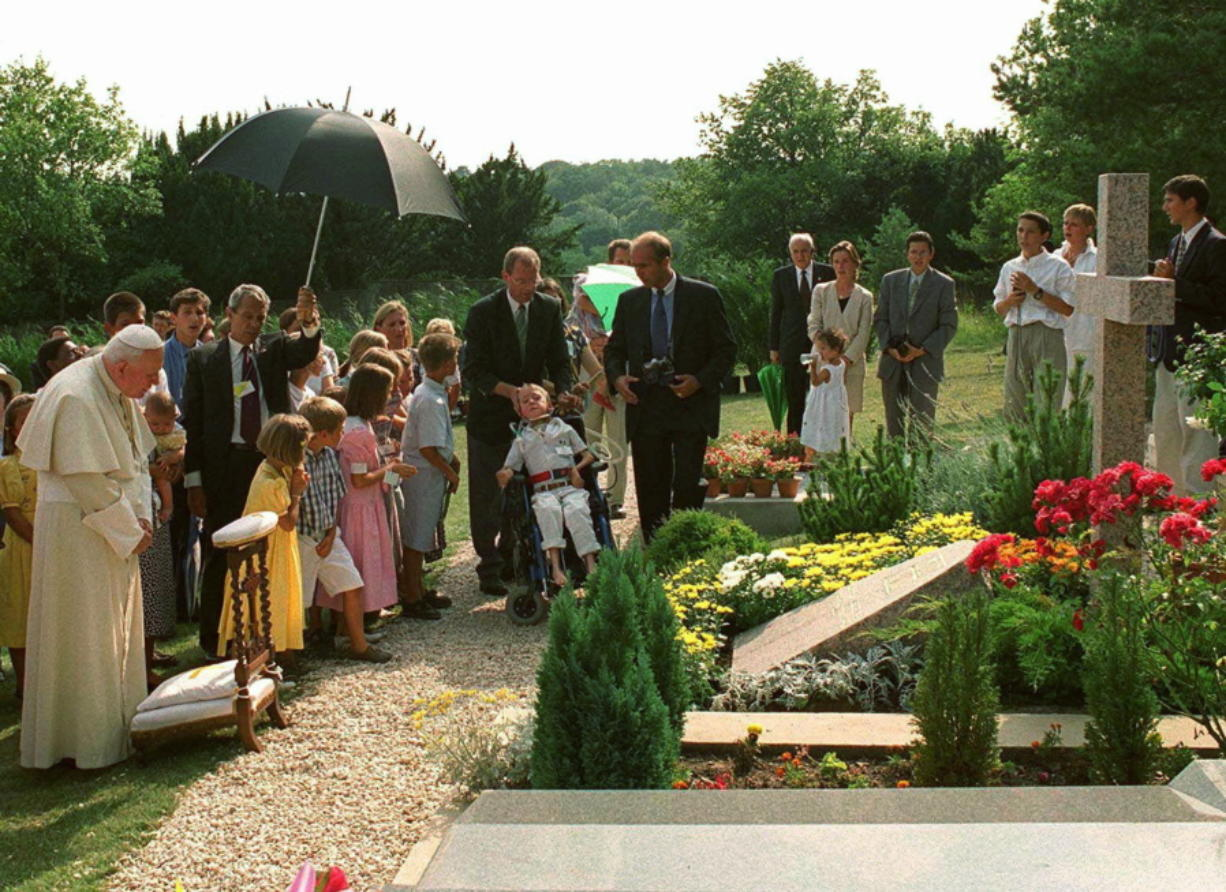 """FILE - In this Aug.22, 1997 file photo, Pope John Paul II meditates by the grave of his former friend geneticist Jerome Lejeune, during a private visit to the Chalo-Saint-Mars cemetery near Paris. Pope Francis on Thursday, Jan. 21, 2021, approved the """"heroic virtues"""" of Dr. Jerome Lejeune, who discovered the genetic basis of Down syndrome, lived from 1926-1994 and was particularly esteemed by St. John Paul II for his anti-abortion stance."""