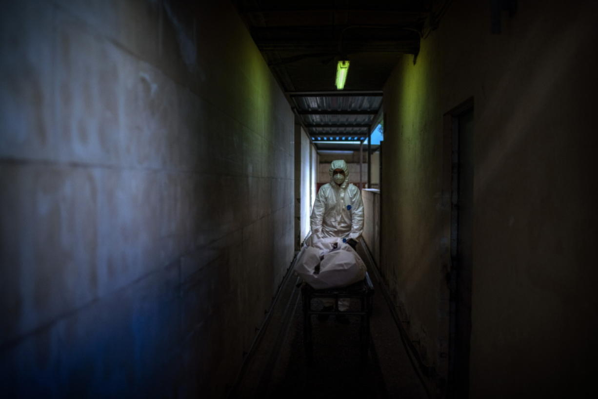 FILE - In this Nov. 5, 2020, file photo, mortuary worker transports the body of a COVID-19 victim on a stretcher at the morgue of a hospital in Barcelona, Spain.