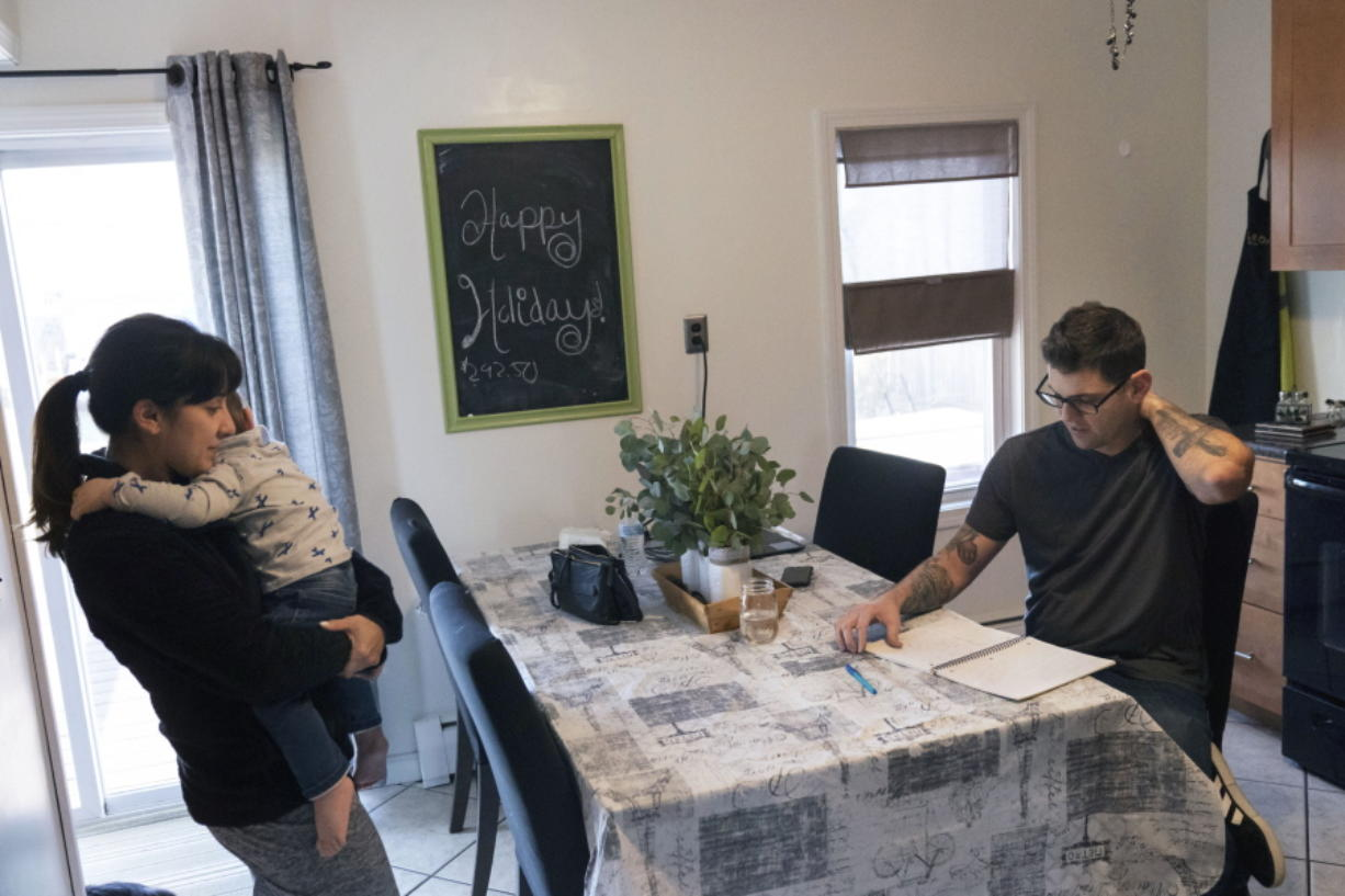 Comedian Brad Pierce, right, looks over the notebook us uses to write jokes as he sits in the kitchen next to his wife, Carmen, and their nephew, Maddox, 1, in West Warwick, R.I., Friday, Jan. 8, 2021. Pierce was finally doing well with his comedy when the pandemic hit. Now he wonders if he can possibly build up his career again. He has a friend who drives for Amazon and fears having to get a job like that while talking about the good old days when he was an entertainer.