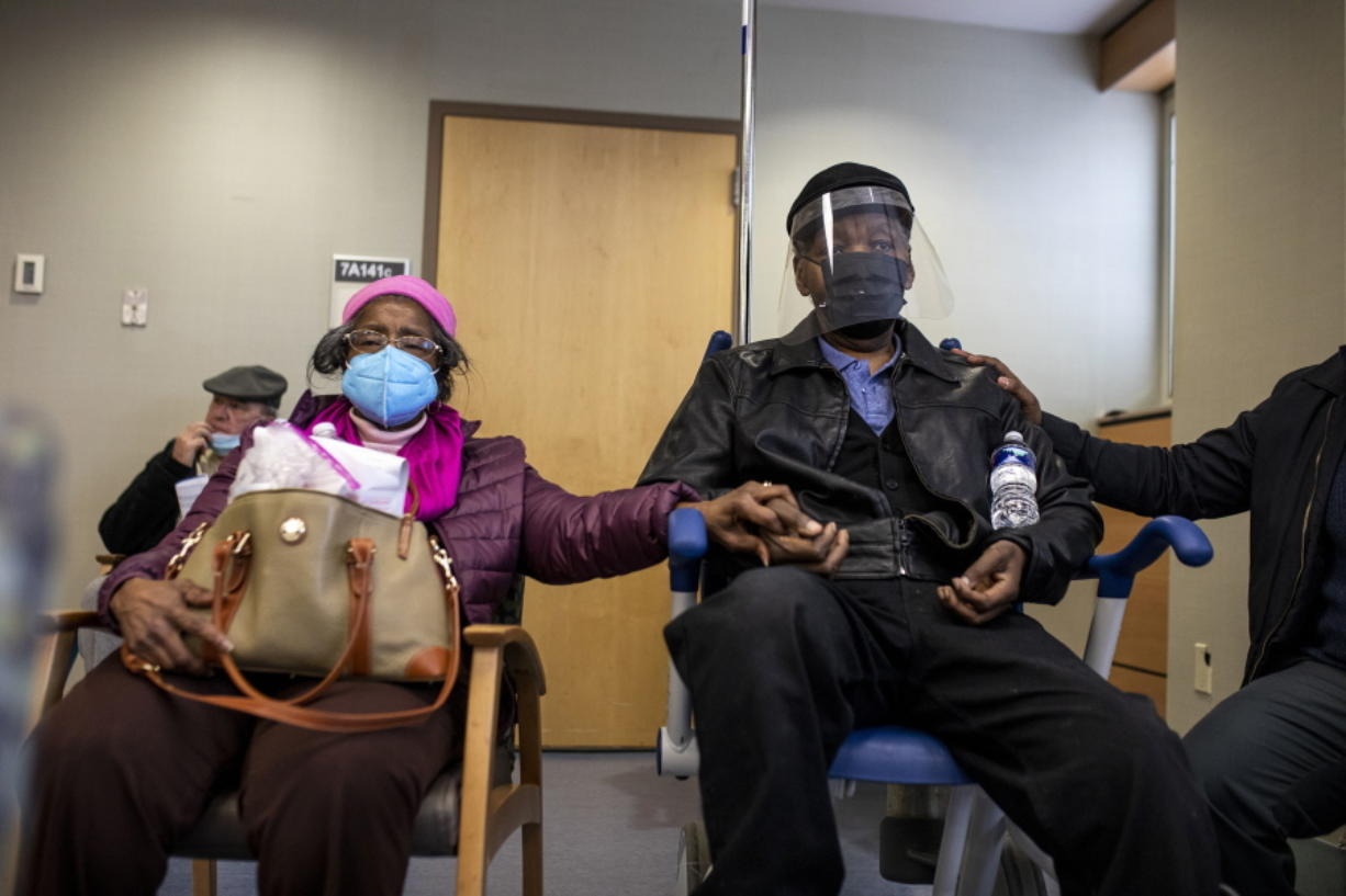 FILE - In this Jan. 23, 2021, file photo, Dorothy Kade, left, holds the hand of her husband, Walter Kade Jr., as they wait in the observation room after he received a COVID-19 vaccine at the VA Medical Center, in Philadelphia.