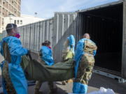 FILE - In this Jan. 12, 2021 photo provided by the Los Angeles County Department of Medical Examiner-Coroner, National Guard members assisting with processing COVID-19 deaths, placing them into temporary storage at the medical examiner-coroner's office in Los Angeles. The seven-day rolling average of daily deaths is rising in 30 states and the District of Columbia, and on Monday, Jan 18, 2021, the U.S. was approaching 398,000, according to data collected by Johns Hopkins University, by far the highest of any country in the world.