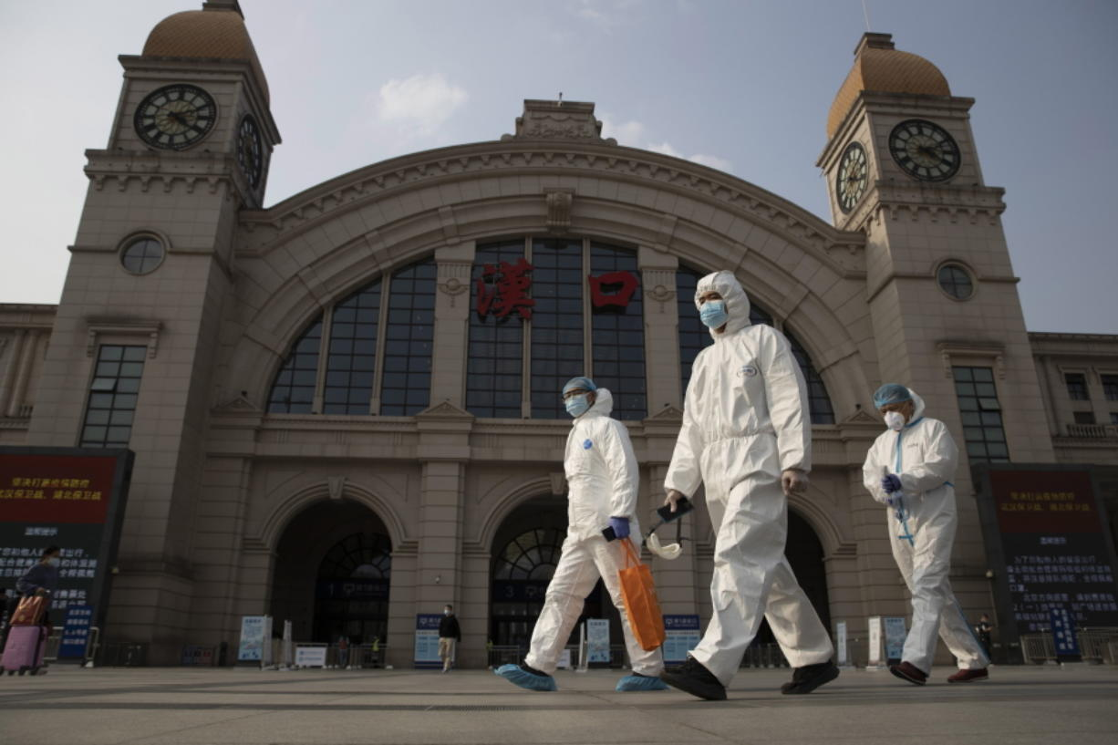 FILE - In this April 7, 2020, file photo, workers in protective suits walk past the Hankou railway station on the eve of its resuming outbound traffic in Wuhan in central China's Hubei province. China says a group of experts from the World Health Organization are due to arrive Thursday, Jan. 14, 2021, for an investigation into the origins of the coronavirus pandemic. A one-sentence announcement from the National Health Commission on Monday, Jan.