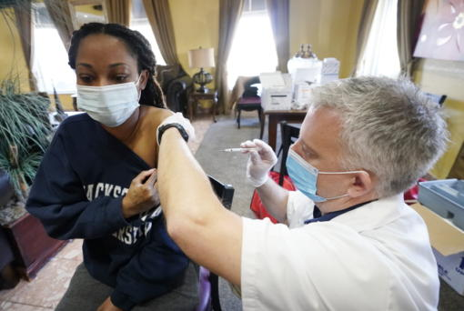 FILE - In this Jan. 12, 2021, file photo, Walgreens pharmacist Chris McLaurin prepares to vaccinate Lakandra McNealy, a Harmony Court Assisted Living employee, with the Pfizer-BioNTech COVID-19 vaccine in Jackson, Miss. The coronavirus vaccines have been rolled out unevenly across the U.S., but some states in the Deep South have had particularly dismal inoculation rates. (AP Photo/Rogelio V.