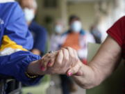 FILE - In this Jan. 12, 2021, file photo residents Ken Fishman, 81, left, and Esther Wallach, 82, right, hold hands as they wait in line for the Pfizer-BioNTech COVID-19 vaccine at the The Palace assisted living facility in Coral Gables, Fla. An ongoing study suggests that older American adults are showing resilience and perseverance despite struggles with loneliness and isolation during the pandemic.