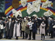 People wearing protective masks to help curb the spread of the coronavirus wait for traffic light to walk along pedestrian crossings in the Shibuya area of Tokyo Tuesday, Jan. 5, 2021. Japanese Prime Minister Yoshihide Suga says vaccine approval is being speeded up to curb the spread of the coronavirus, and he promised to consider declaring a state of emergency. The Japanese capital confirmed more than 1200 new coronavirus cases on Tuesday.