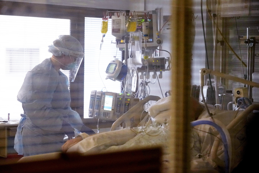 Registered nurse Andraya Zelle treats a patient in the COVID intensive care unit at UW Medical Center-Montlake, Tuesday, Jan. 26, 2021, in Seattle. King County, where the hospital is located, has been on a downward trend of COVID-19 cases after two-and-a-half straight months of increases. But the current lull could be, and some experts believe will be, upended as more contagious variants of the virus spread throughout United States.