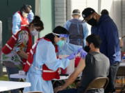 FILE - In this Jan. 13, 2021, file photo, health care workers receive a COVID-19 vaccination at Ritchie Valens Recreation Center, Wednesday, Jan. 13, 2021, in Pacoima, Calif. The rapid expansion of vaccinations to senior citizens across the U.S. has led to bottlenecks, system crashes and hard feelings in many states because of overwhelming demand for the shots.