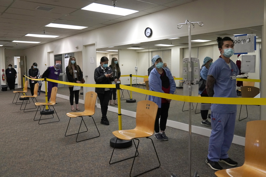 FILE - In this Dec. 24, 2020, file photo, healthcare workers wait in line to receive the Pfizer-BioNTech COVID-19 vaccine at Seton Medical Center in Daly City, Calif. The rapid expansion of vaccinations to senior citizens across the U.S. has led to bottlenecks, system crashes and hard feelings in many states because of overwhelming demand for the shots.