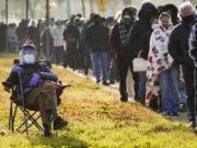 FILE - In this Jan. 11, 2021, file photo, Florence Mullins, 89, sits in a chair as a family member holds her place in a long line to receive a COVID-19 vaccine at Fair Park in Dallas. Uncertainty over the pace of federal COVID-19 vaccine allotments triggered anger and confusion Friday, Jan. 15, 2021, in some states where officials worried that expected shipments would not be forthcoming.  (Smiley N.