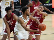 Colorado guard D'Shawn Schwartz, front, passes the ball as Washington State center Dishon Jackson, left, and forward DJ Rodman defend during the second half of an NCAA college basketball game Wednesday, Jan. 27, 2021, in Boulder, Colo.