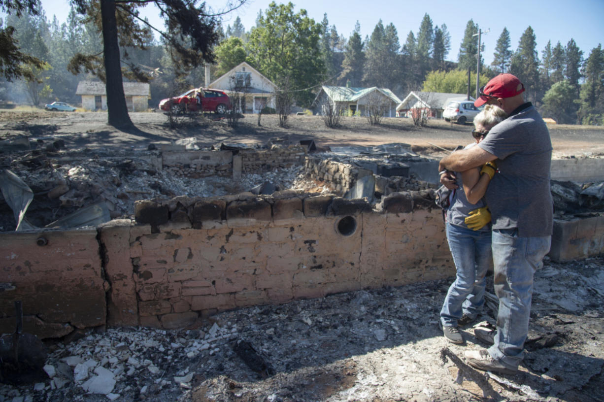 Shawn Thornton hugs his wife, Shannon Thornton, next to the rubble of their burned home Tuesday, Sept. 8, 2020, in Malden, Washington the day after a fast-moving wildfire swept through the tiny town west of Rosalia. Shawn and Shannon weren't home at the time, but their son Cody was and managed to get their dog and a few belongings before leaving just minutes before the flames swept through.