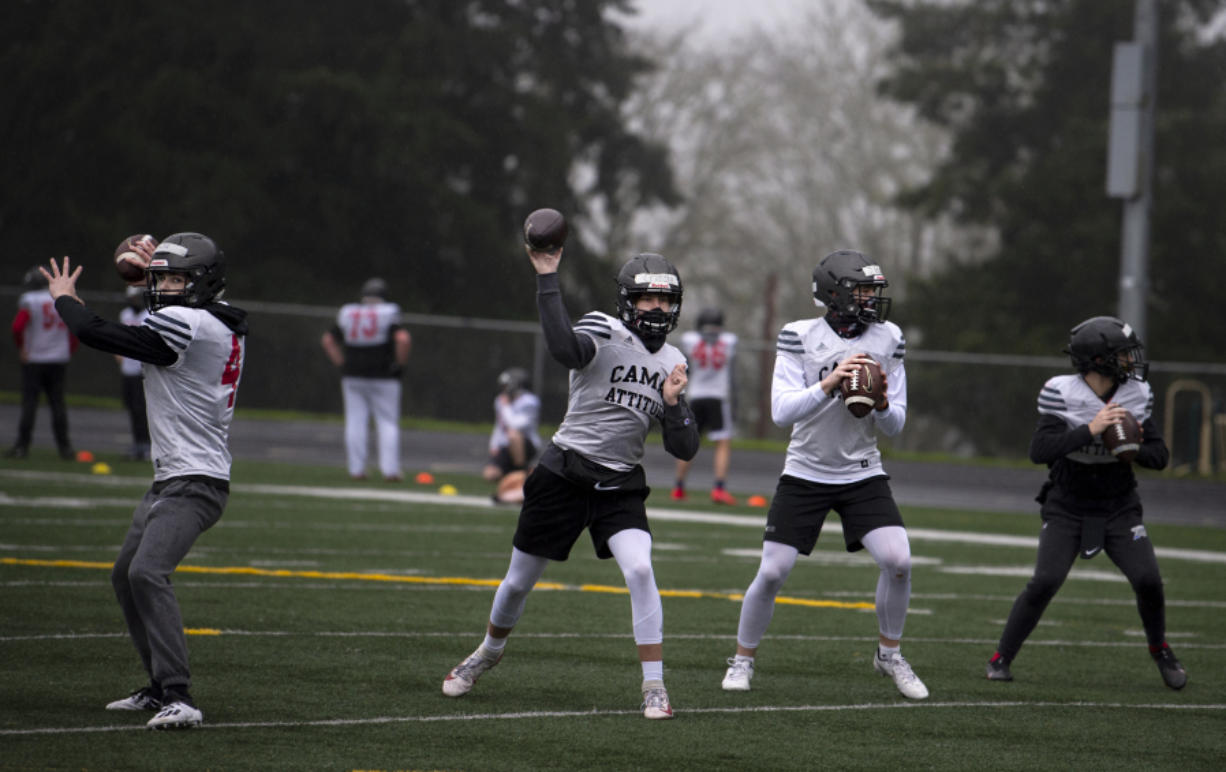 Camas quarterbacks, including Nathan Criddle, left center, and Jake Blair, right center, throw during a drill on Monday at Camas High School. Official practices began across Clark County on Monday as the return of high school sports nears.