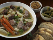 Pot au feu (boiled meats dinner) is served with accompaniments like carrots, pearl onions, fresh herbs, pickles, mustard.