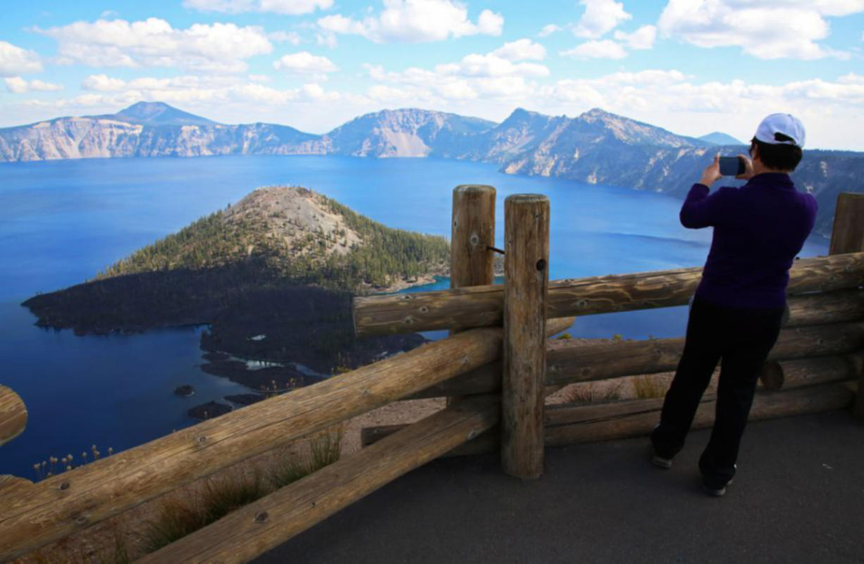 A visitor takes a picture at the Watchman Overlook.