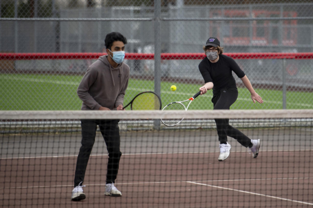 Mountain View senior Nathaniel John, left, watches his Skyview opponents while senior Bryce Penick hits a return in a 3A/4A Greater St. Helens League boys tennis match on Monday at Union High School. Monday was the first time in 333 days that local high school sports held competitions.